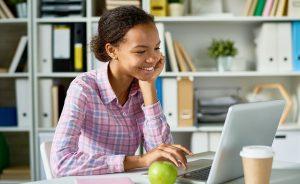 Menina estudando em uma biblioteca através de um computador