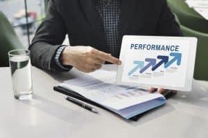 homem-de-terno-numa-mesa-mostrando-um-papel-escrito-performance_Easy-Resize.com_
